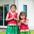 Cute indian girls in sari greeting dressed with folded hands representing traditional standing outside their new house Stock Photo