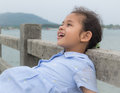 A cute joyful girl on the bridge with sea view Stock Photography