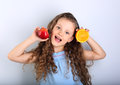 Cute joying grimacing happy kid girl with curly hair style holdi Royalty Free Stock Photo