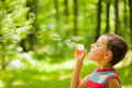Cute kid blowing soap bubbles Royalty Free Stock Photography
