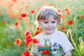 Cute kid boy with poppy flower on poppy field on warm summer day Royalty Free Stock Photo