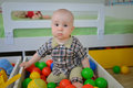 Cute kid or child playing colorful balls looking down Royalty Free Stock Photo