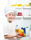 Cute kid choosing food near open refrigerator Stock Image