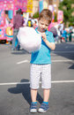Cute kid eating cotton candy over fair background portrait of child a summer festival Stock Photo