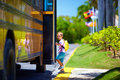 Cute kid is getting on the bus ready to go to school boy Stock Image