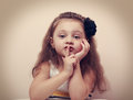 Cute kid girl showing silence sign the finger near lips. Vintage Royalty Free Stock Photo