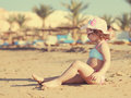 Cute kid girl sunbathing on beach instagram effect Royalty Free Stock Images