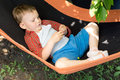 Cute kid lying and playing on the swing close up image of a Royalty Free Stock Photography