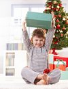 Cute kid raising christmas gift high Stock Photos