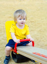 Cute kid on the see saw little boy riding playground Stock Image