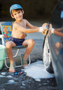 Cute kid washing car with sponge outdoor Royalty Free Stock Photo