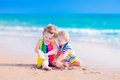 Cute kids playing on the beach happy baby boy and little curly toddler girl brother and sister with a huge sea shell in sand a Royalty Free Stock Photo