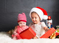 stock image of  Cute kids on rug opening a Christmas present