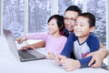 Cute kids watching movie on laptop with dad two cheerful little children enjoy their father by using shot at home Stock Photos