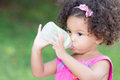 Cute latin girl drinking from a baby bottle with green grass background Royalty Free Stock Photography