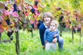 Cute laughing brother and baby sister in vine yard playing together a sunny autumn picking ripe fresh grapes Royalty Free Stock Photo