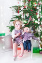 Cute laughing toddler girl and her little baby brother under christmas tree sitting together in a white rocking chair a beautiful Royalty Free Stock Photo
