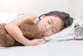 Cute little asian girl sleep and hug teddy bear on bed Royalty Free Stock Photo