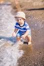 Cute little baby boy exploring the beach at seaside Stock Photos