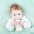 Cute little baby drinking milk formula out of bottle