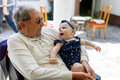 Cute little baby girl with grandfather on summer day in garden Royalty Free Stock Photo