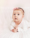 Cute little baby girl with pink flower headband exploring the wo world from couch Royalty Free Stock Image