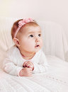 Cute little baby girl with pink headband exploring the world flower from couch Royalty Free Stock Photo