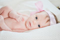 Cute little baby girl staring up white blanket wearing pink strap has big blue eyes Royalty Free Stock Photo