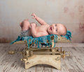 Cute little baby with legs up on scales Royalty Free Stock Photo