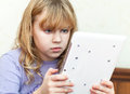Cute little blond girl using white tablet pc Stock Photography