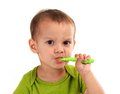 Cute little boy brushing teeth, isolated on white Royalty Free Stock Photo