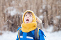 Cute little boy, catching snowflakes in the park on a winter day Royalty Free Stock Photo
