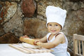 Cute little boy with chef hat cooking Stock Photos