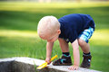 Cute little boy climbing a wall blond over low cement with yellow plastic trowel in his hand Royalty Free Stock Photos