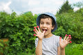 Cute little boy eats a berries from his fingers and smiles Royalty Free Stock Photo