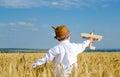 Cute little boy flying a toy plane in a wheatfield Royalty Free Stock Photo