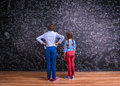 Cute little boy and girl in front of a big blackboard. Royalty Free Stock Photo