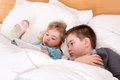 Cute little boy and girl reading before sleeping a bedtime story on a tablet pc lying in a big comfortable bed together Royalty Free Stock Photos