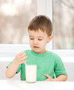 Cute little boy with a glass of milk is dipping his tongue in the Stock Photography