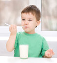 Cute little boy with a glass of milk is dipping his tongue in the Stock Image