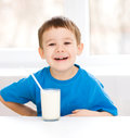 Cute little boy with a glass of milk is dipping his tongue in the Stock Photo