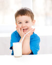 Cute little boy with a glass of milk is dipping his tongue in the Stock Photos