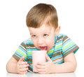 Cute little boy with a glass of milk is dipping his tongue in the isolated over white Stock Photos