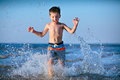 Cute little boy having fun at the beach running through water Stock Photo