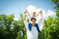 Cute little boy on his father s shoulders against a background of sky and green forest in summer warm day in the summer Stock Photo
