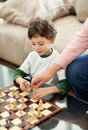 Cute little boy and his grandmother playing chess Stock Images