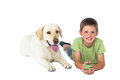 Cute little boy holding ball lying on floor with his labrador white background Stock Photos