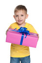 Cute little boy holds a gift box against the white background Royalty Free Stock Image