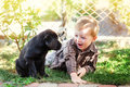 Cute little boy kneeling with his puppy labrador smiling at camera Royalty Free Stock Photo