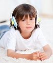 Cute little boy listening music lying on floor Royalty Free Stock Photo